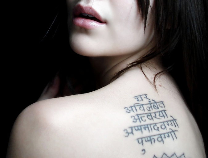 sanskrit writing tattoo on upper back